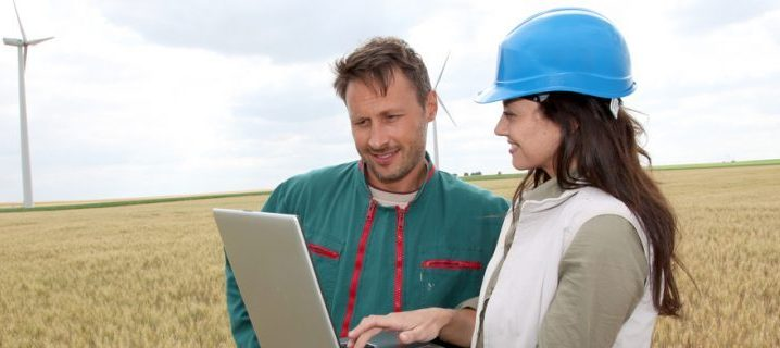 2 people in field with laptop and windmills